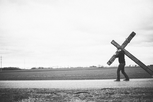 Man carrying cross down road