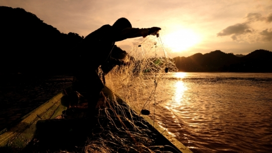 fisherman-throwing-net-from-boat